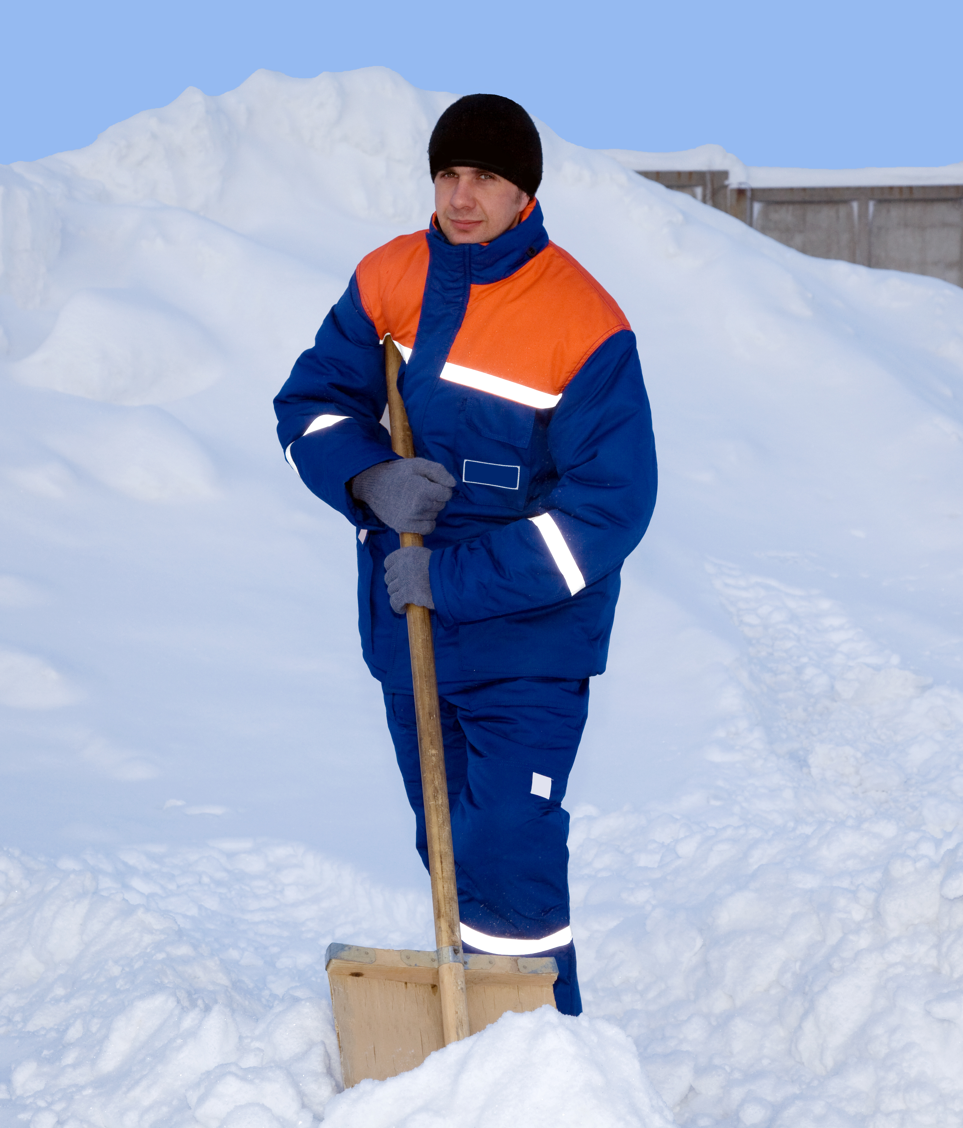 Worker in the winter suit consisting of a jacket and trousers against the backdrop of the snow